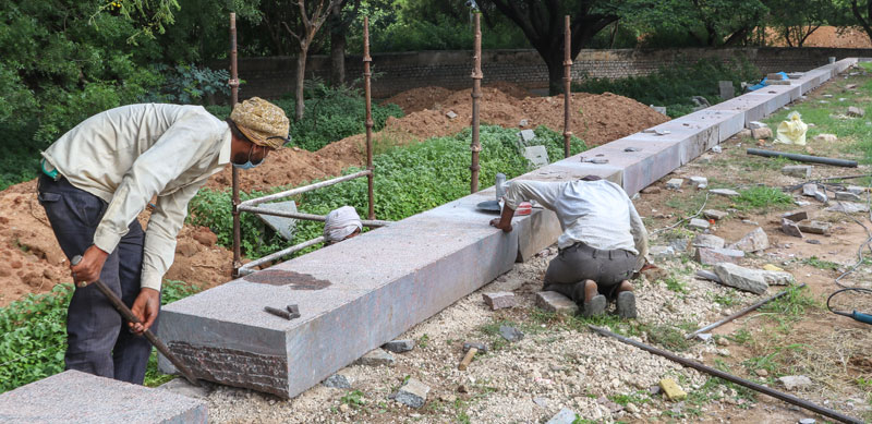 Stone craftsmen installing hand chiselled granite stone on the plinth of the Tomb of Abdullah Qutb Shah