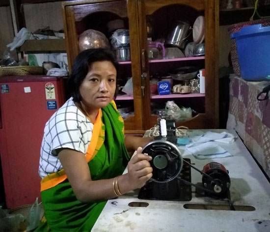 Anandi with her solar-powered sewing machine, sewing a face mask