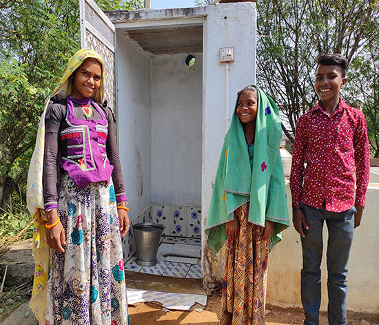 Vagtu Bai's daughter-in-law, nephew and niece pose in front of their toilet