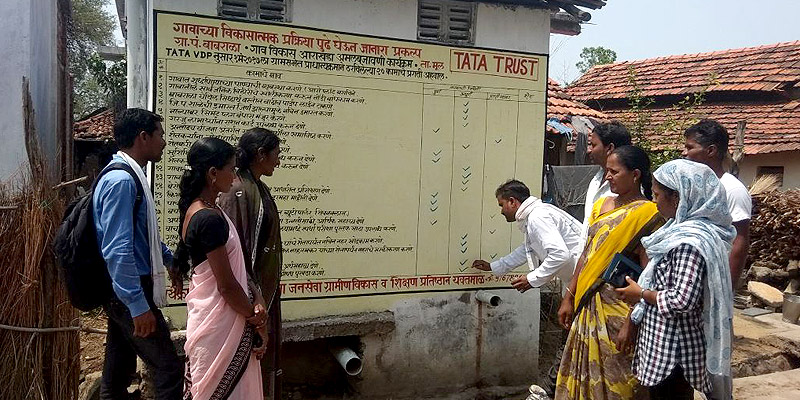 Community members using wall-paintings to track progress in achieving priority line items in their Village Development Plan