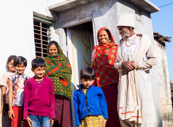 A family poses beside their newly constructed toilet