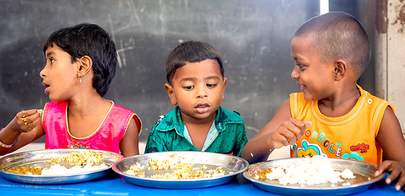 Children enjoying their mid-day meal of fortified rice