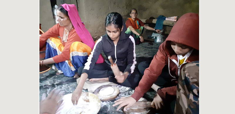 Children learning to cook with local women